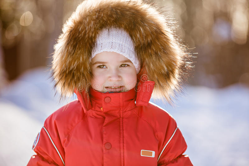 Kleines sehr nettes Mädchen in einer roten Klage mit Pelzhaubenwinter auf dem b lizenzfreie stockfotografie