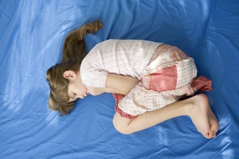 Kleines trauriges Mädchen, das auf Bett liegt. lizenzfreies stockfoto