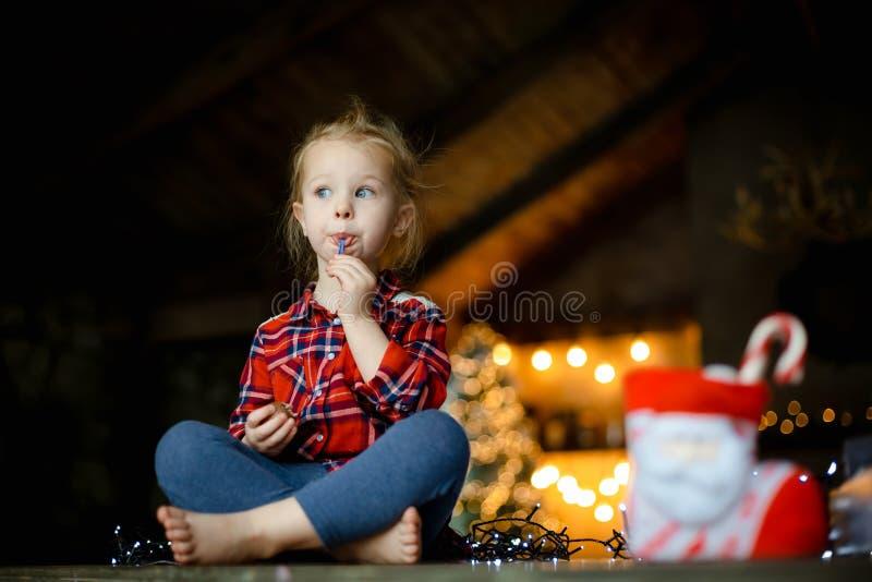 Kleines weißes blondes Mädchen, das auf einem Holztisch im Wohnzimmer des Chalets, verziert für Weihnachtsbaum- und Girlandenespr stockfoto