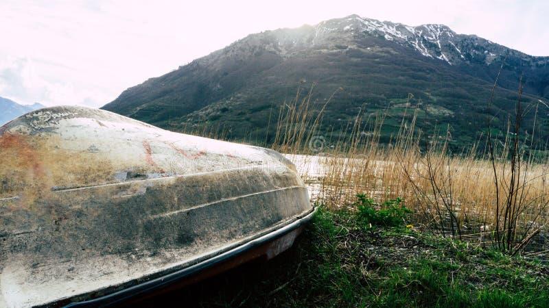 Kleines wei?es Boot drehte sich umgedreht mit schmutziger Unterseite und Kiel auf K?ste mit Meer und Bergen an der Vorderansicht  stockfotos