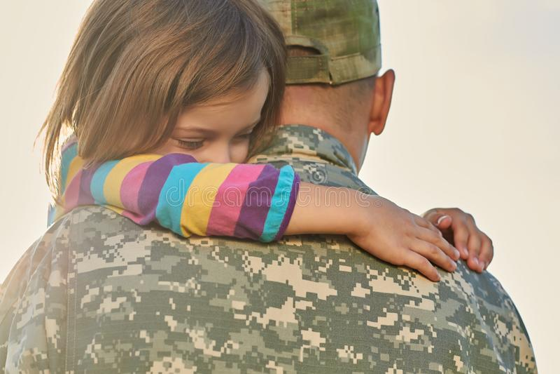 Kleines weibliches Kind umarmt einen Soldaten stockfotografie