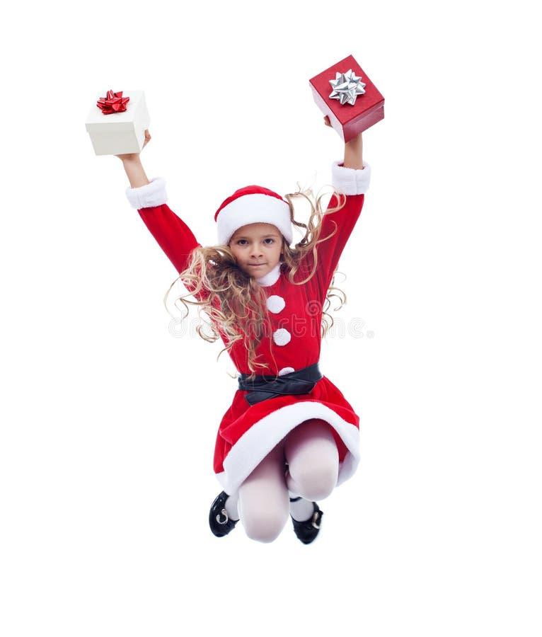 Kleines Weihnachtsmann-Mädchen, das hoch mit Geschenken springt stockfoto