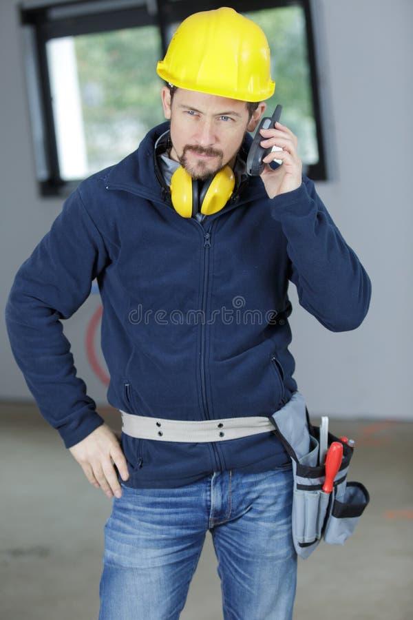 Kleinhandelaar die aandachtig aan walkie-talkie luisteren stock fotografie