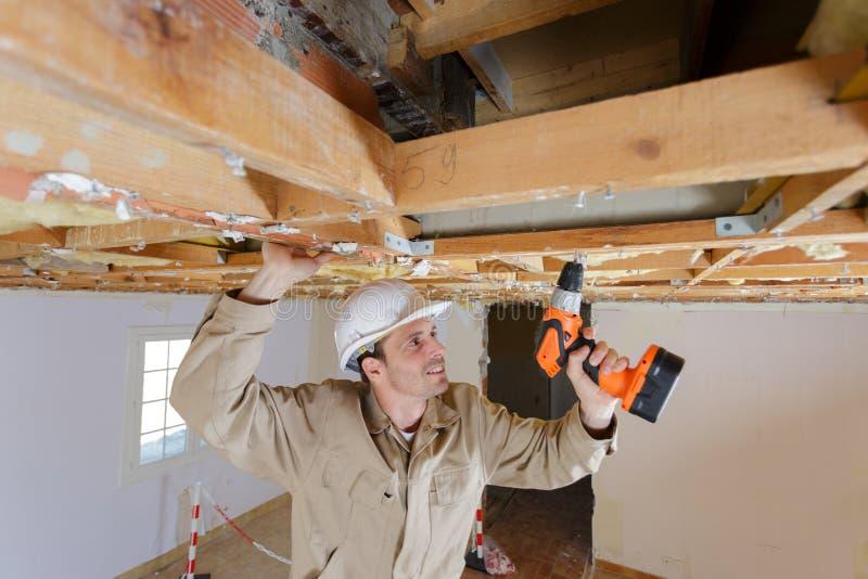 Kleinhandelaar die boor op houten kader voor plafond gebruiken stock afbeelding