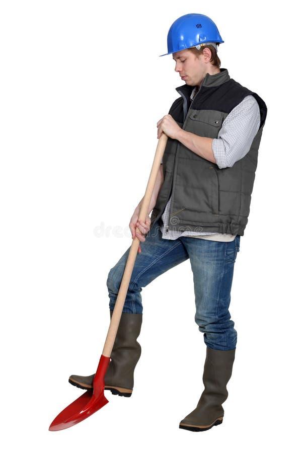 Kleinhandelaar die een spade gebruiken royalty-vrije stock afbeelding