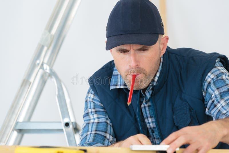 Kleinhandelaar die met potlood in mond werken stock fotografie