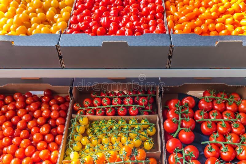 Kleinhandelsvertoning van diverse verse gele, oranje en rode tomaten stock afbeeldingen