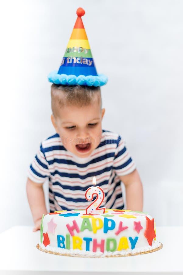 Kleinkind brennt eine Kerze auf dem Kuchen auf seinem Geburtstag durch stockbild