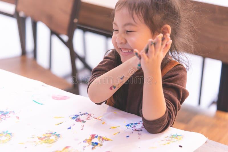 Kleinkind, das beim Erhalten unordentlich mit Kunstwerk creativ lacht lizenzfreie stockfotografie