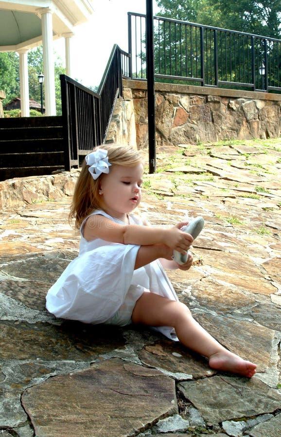 Kleinkind, das ein Schuhe setzt lizenzfreies stockfoto