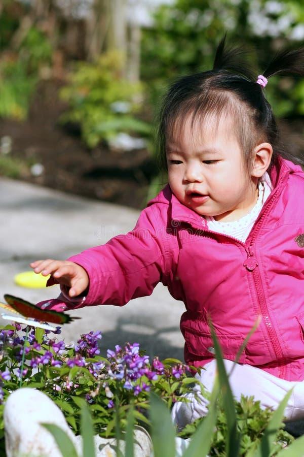 Kleinkind, das im Garten spielt lizenzfreie stockbilder