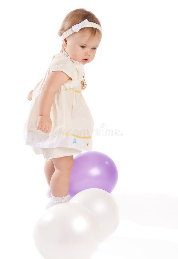 Kleinkind, das mit Ballonen spielt stockfotografie