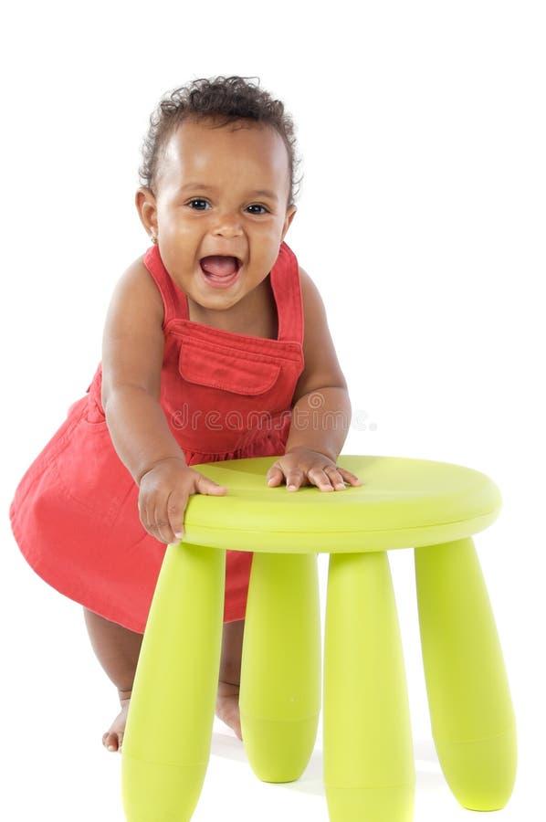 Kleinkind, das mit einem Stuhl spielt lizenzfreies stockbild