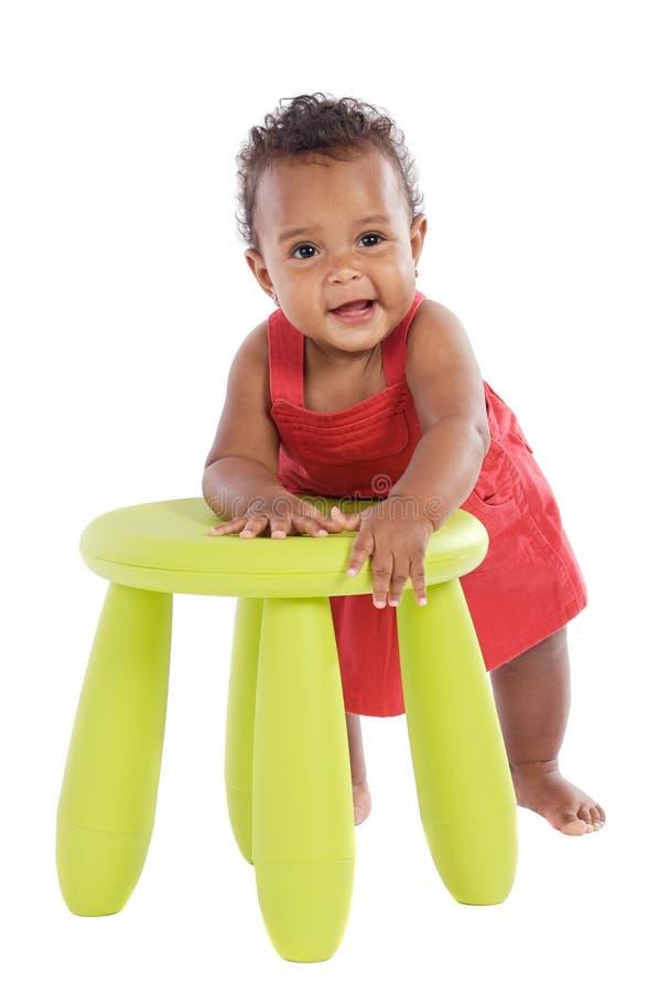 Kleinkind, das mit einem Stuhl spielt stockbilder