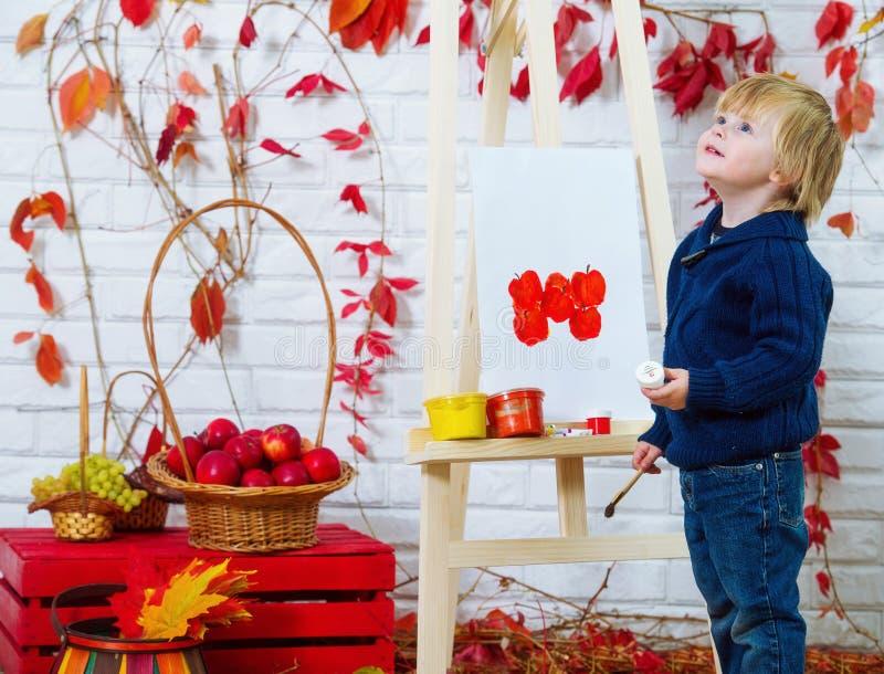 Kleinkind, das rote Äpfel malt stockfotos