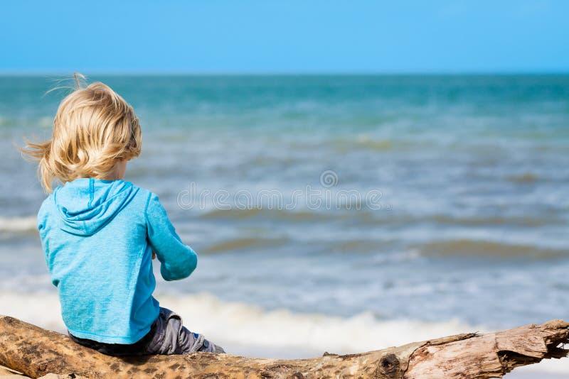 Kleinkind, das am Strand sitzt stockbilder
