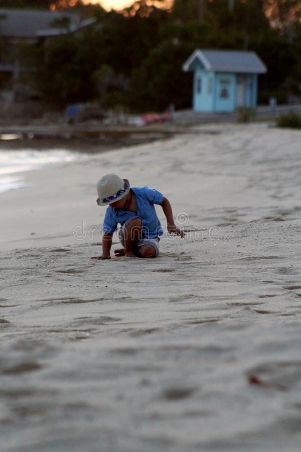 Kleinkind, das am Strand spielt stockfotografie