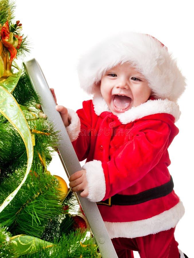 Kleinkind, das Weihnachtsbaum verziert stockfoto