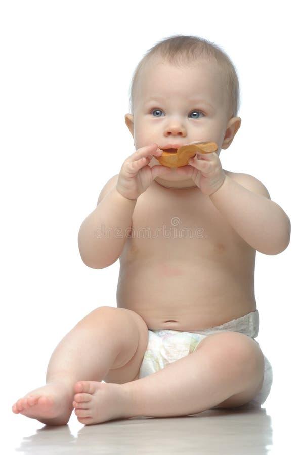 Kleinkind in der Windel, die mit spielt, wodden Löffel lizenzfreies stockfoto