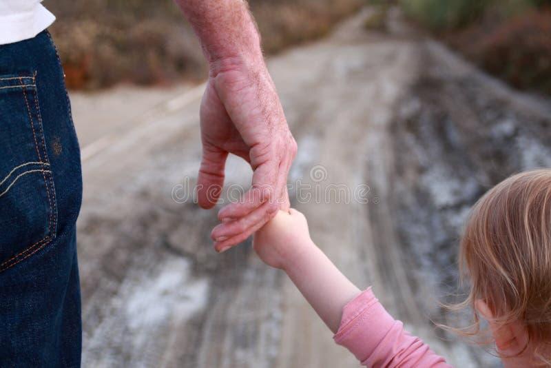 Kleinkind hält den Finger des Vatis stockbilder