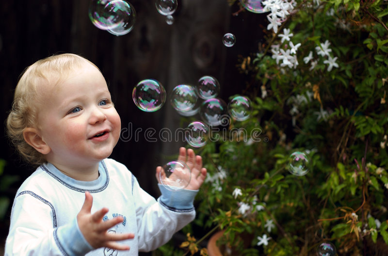 Kleinkind-Junge, der mit Luftblasen spielt stockfotos