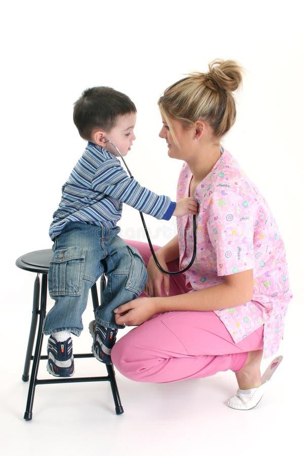 Kleinkind-Junge, der zum Inneren der Krankenschwester hört stockfotos