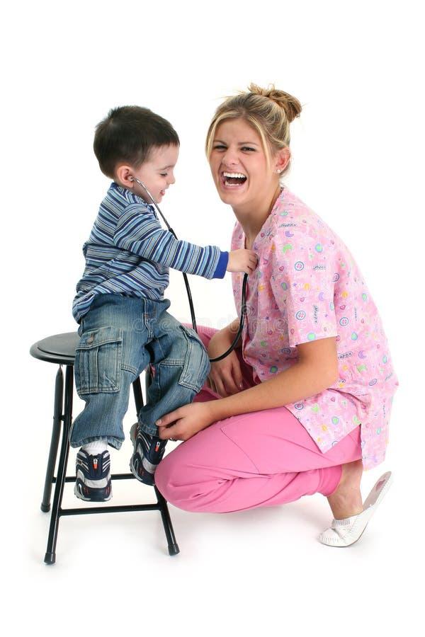 Kleinkind-Junge, der zum Inneren der Krankenschwester hört lizenzfreie stockbilder