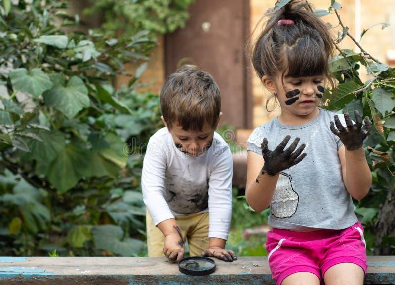 Kleinkind-Junge und kleines Mädchen - schmutzig vom Spielen im Schlamm lizenzfreies stockfoto