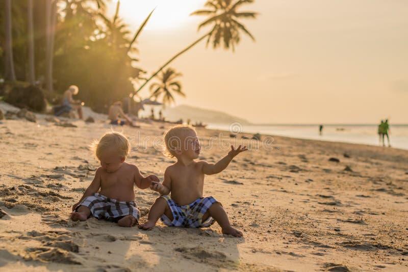 Kleinkind-Jungen, die auf dem Strand sitzen lizenzfreies stockfoto