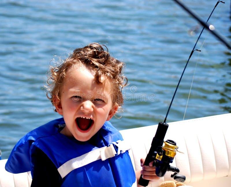 Kleinkind-Jungenfischen auf einem Boot stockbilder