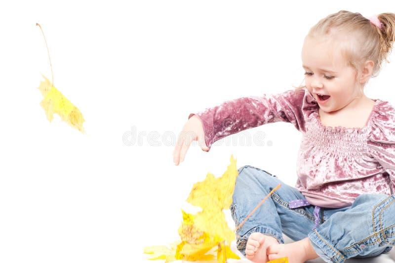 Kleinkind mit Ahornblättern stockfotografie