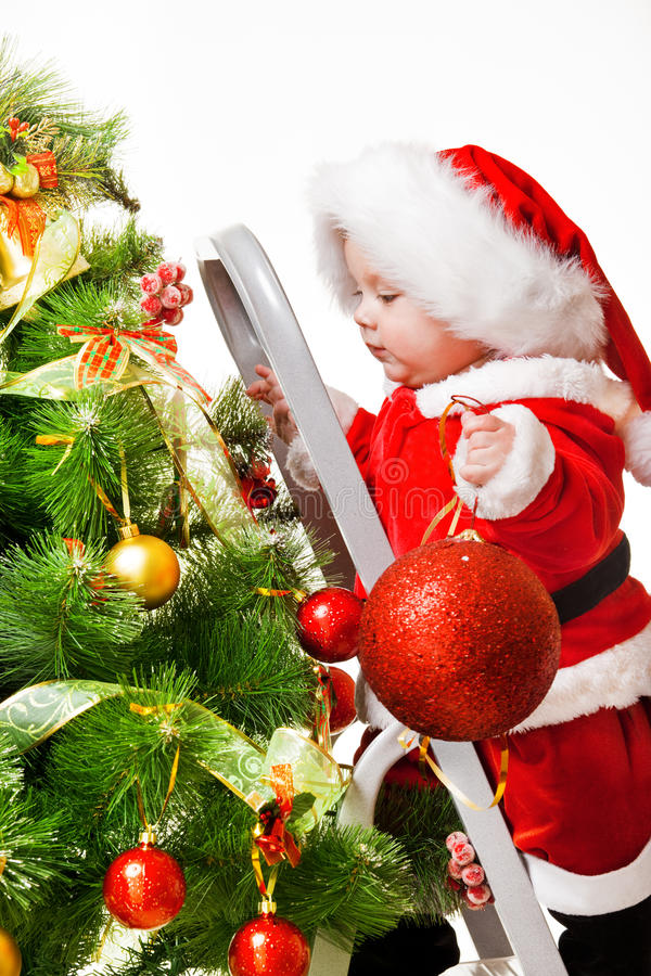 Kleinkind mit einer Weihnachtskugel stockfotografie