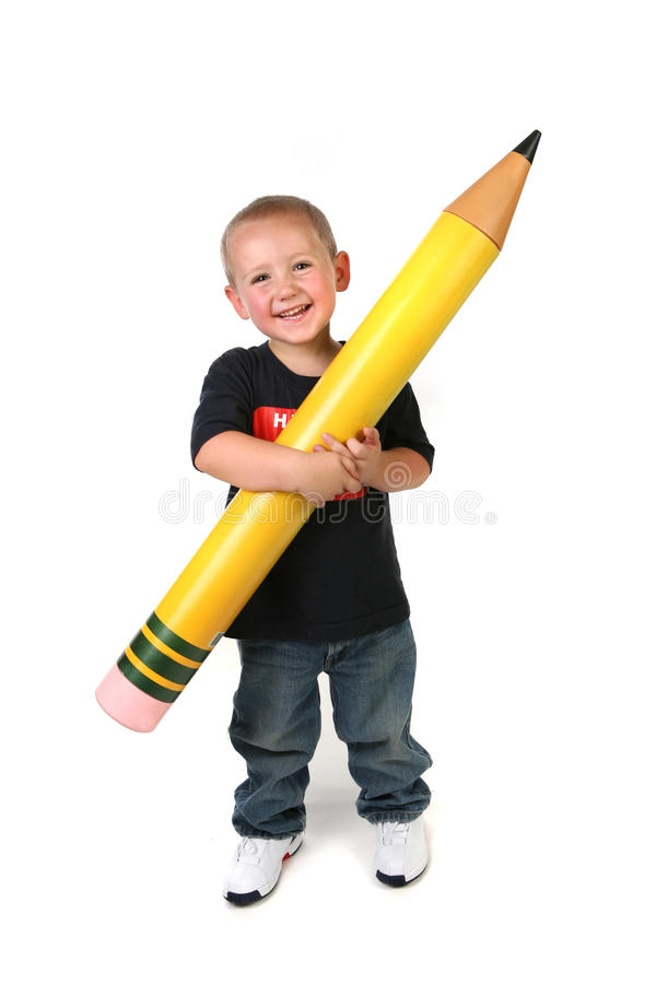 Kleinkind-schulpflichtiges Kind, das großen Bleistift anhält lizenzfreies stockbild