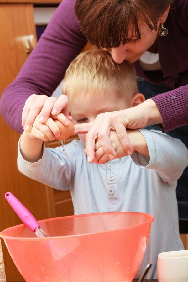Kleinkind- und Mutterkochen, Kuchen in der Schüssel machend stockfotos