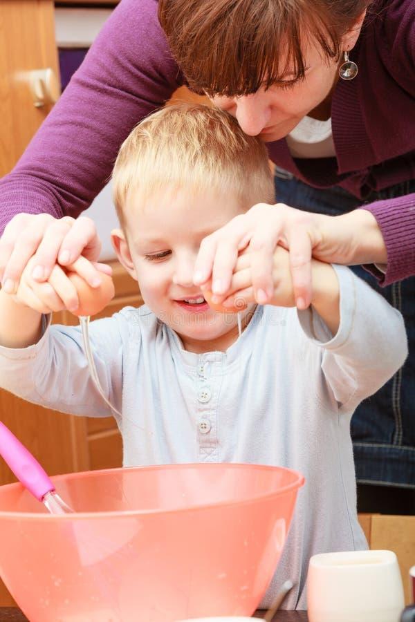 Kleinkind- und Mutterkochen, Kuchen in der Schüssel machend stockfotografie