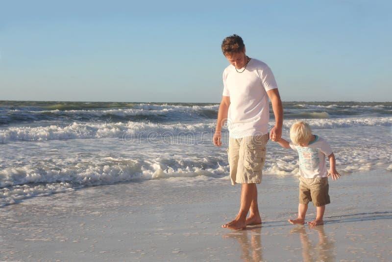 Kleinkind, welches die Hand des Vaters beim Gehen in Ozean auf Strand hält lizenzfreies stockfoto