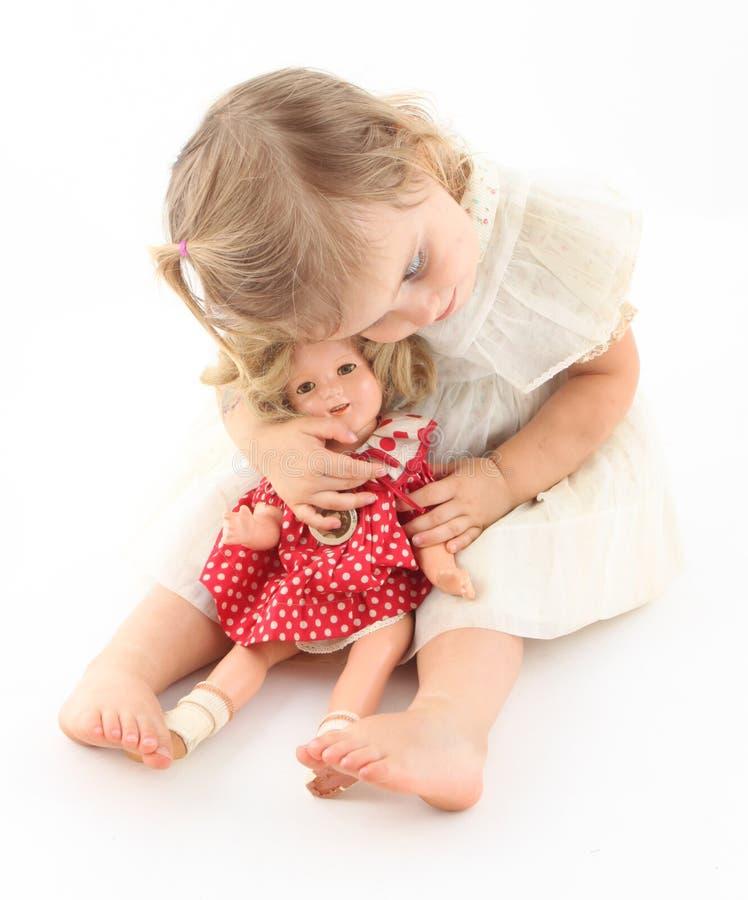 Kleinkindbaby, das ihre kostbare Puppe sich anschmiegt stockbilder