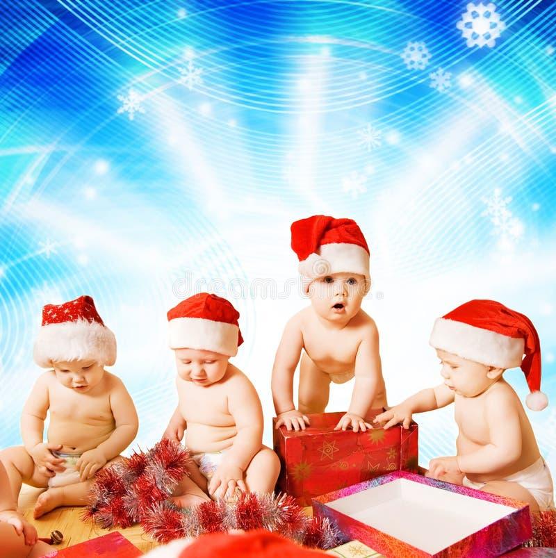Kleinkinder in den Weihnachtshüten stockfotos