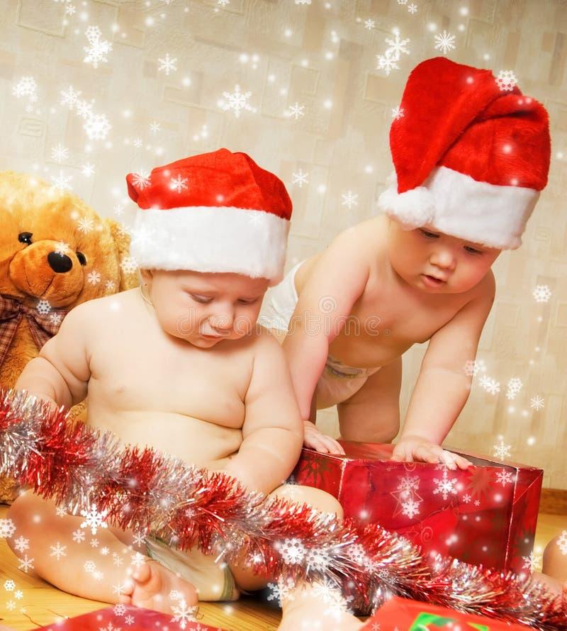 Kleinkinder in den Weihnachtshüten stockfotografie