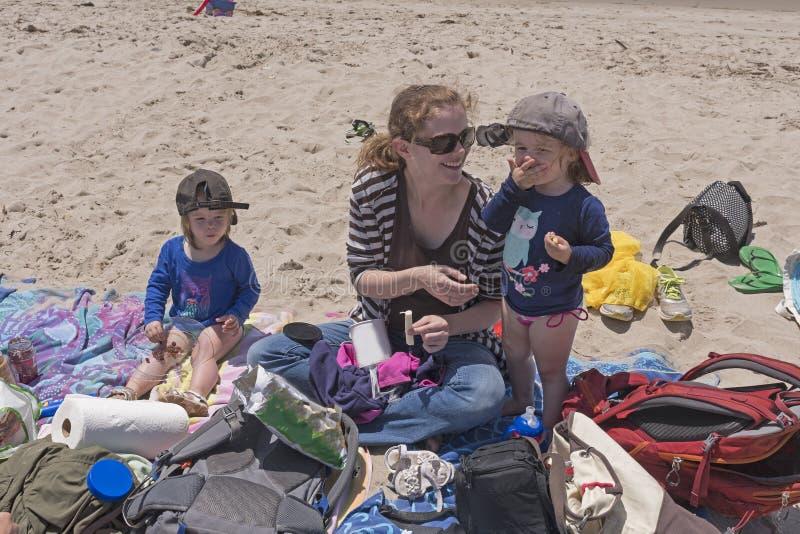 Kleinkinder, die das Mittagessen auf dem Strand essen stockfotos