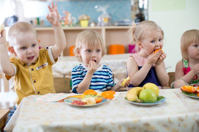 Kleinkinder, die im Kindergarten essen lizenzfreie stockbilder