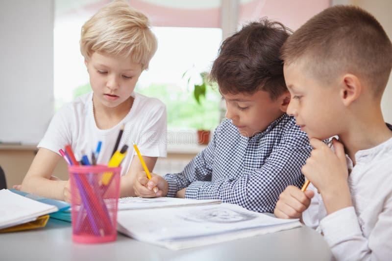 Kleinkinder, die am Volksschulekunstunterricht zeichnen stockbild