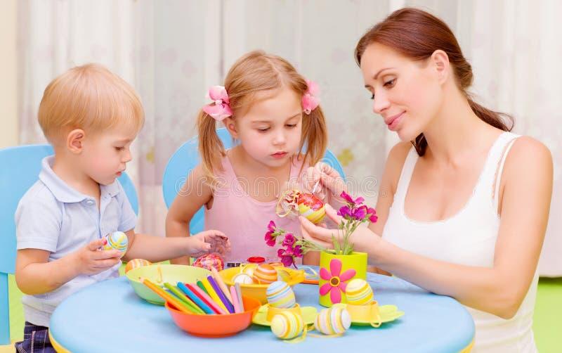 Kleinkinder mit Lehrer gemalten Ostereiern stockbilder
