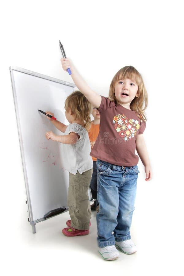 Kleinkinder nahe weißem Vorstand lizenzfreie stockfotografie