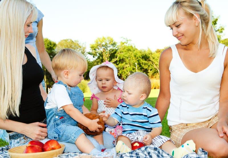 Kleinkinder und ihre Mammen, die zu Mittag essen stockfotografie