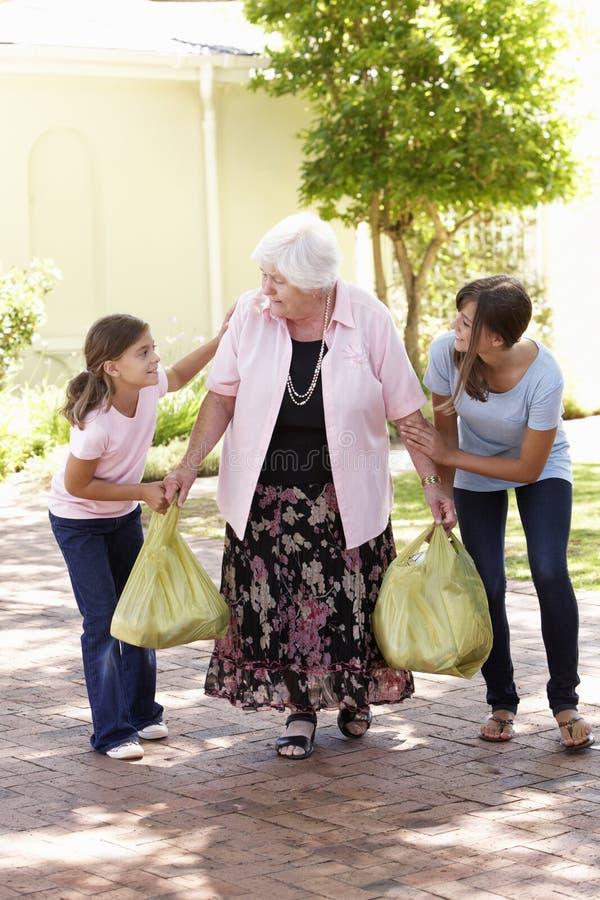 Kleinkinderen die Grootmoeder helpen aan Carry Shopping stock foto's
