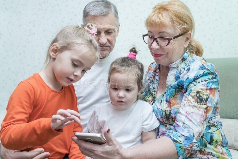 Kleinkinderen die grootmoedersmartphone bekijken stock afbeelding