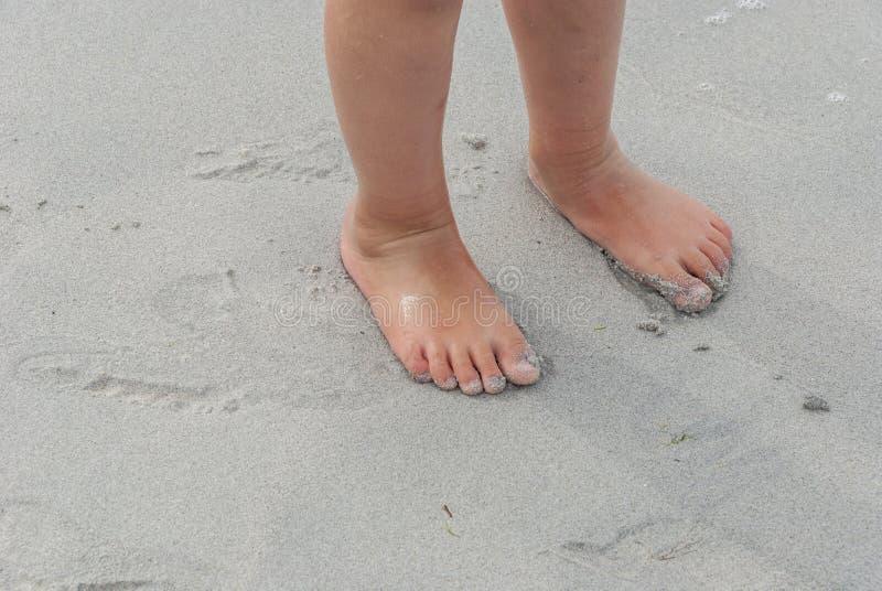 Kleinkindfüße auf dem sandigen Strand lizenzfreie stockbilder