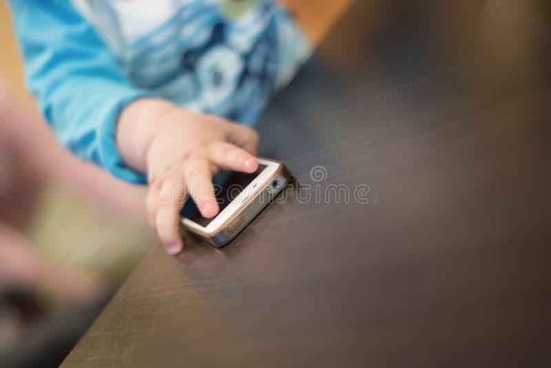 Kleinkindhand, die Handy von der Tabelle nimmt lizenzfreie stockfotografie