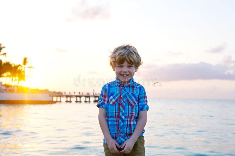 Kleinkindjunge bei Sonnenuntergang nahe Ozean lizenzfreies stockbild